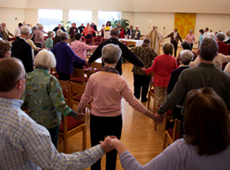 Sunday Assembly ecumenical worshipers holding eachother's hands in prayer