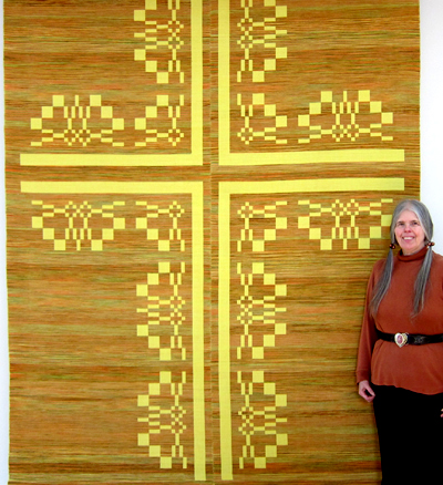 Pat Hilts standing beside her large tapestry weaving of a floral edged cross in gold