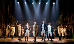 Hamilton and friends singing out on stage on Brodway