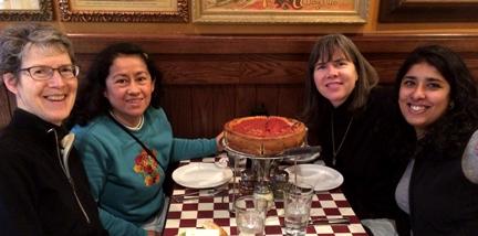4 sisters gathered around deep-dish pizza